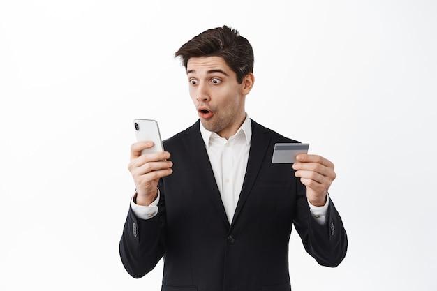 Hombre de negocios emocionado en traje mira su teléfono, lee la pantalla con cara de asombro y sostiene una tarjeta de crédito, inicie sesión en la aplicación de banca en línea, de pie sobre una pared blanca
