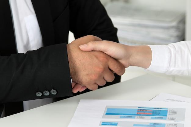 Hombre de negocios y empresaria dándose la mano, terminando una reunión. vista de primer plano.