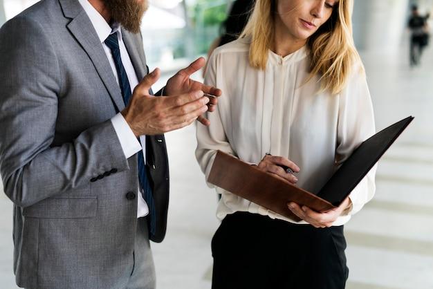 Un hombre de negocios y una empresaria que tienen una charla de negocios, escribiendo una agenda de negocios en un cuaderno