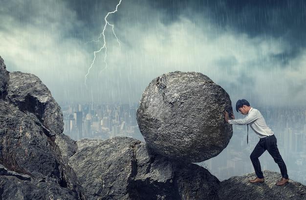 Hombre de negocios empujando piedra grande hasta la colina, tareas pesadas de negocios y concepto de problemas.