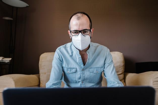 Hombre de negocios enfermo en máscara blanca trabajando remotamente desde casa