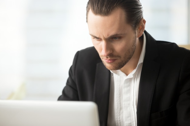 Hombre de negocios enfocado que mira en la pantalla de la computadora portátil