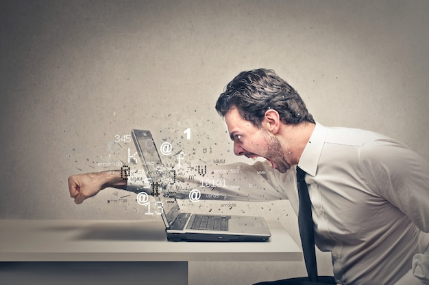 Hombre de negocios enojado aplastando su computadora portátil