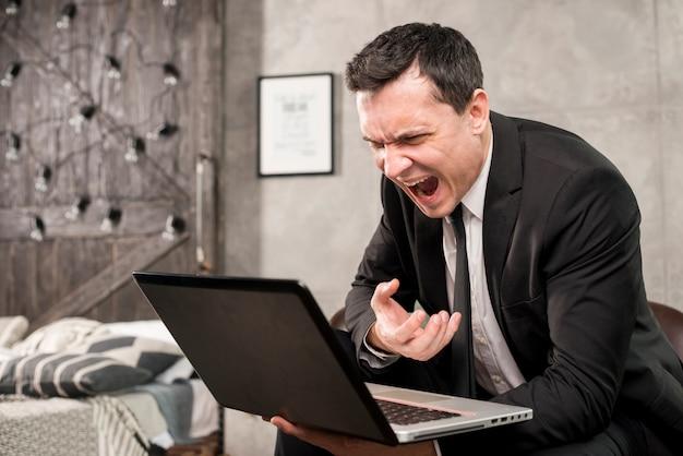 Hombre de negocios enojado que grita en el ordenador portátil en casa