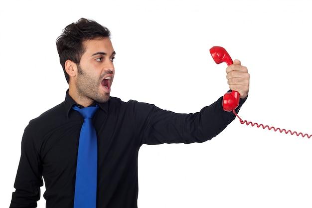 Hombre de negocios enojado que grita en el teléfono aislado en el fondo blanco