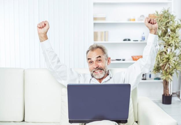 Hombre de negocios entusiasta con un portátil abierto sentado en un sofá blanco en una oficina moderna