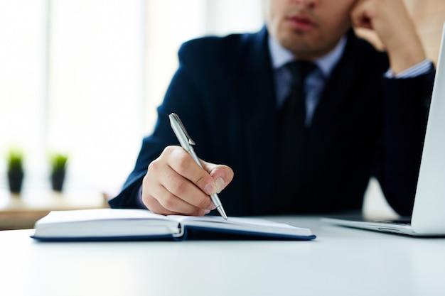 Hombre de negocios escribiendo en cuaderno diario