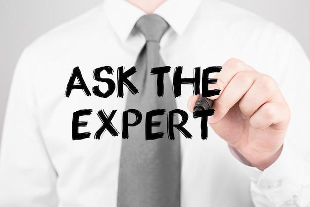 Hombre de negocios escribiendo palabra pregunte al experto con marcador, concepto de negocio
