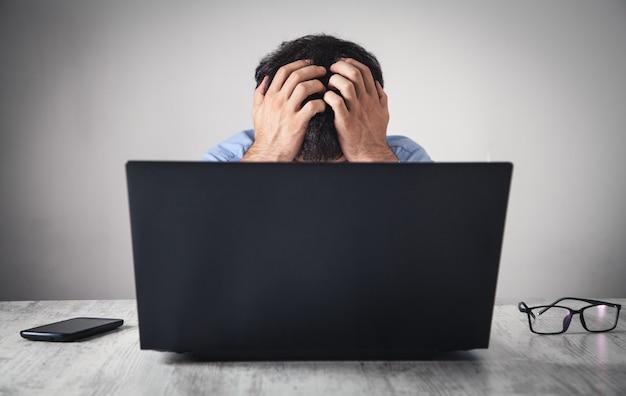 Hombre de negocios estresado caucásico sentado y cubriendo la cara en la oficina.