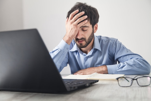 Hombre de negocios estresado caucásico sentado en la oficina.