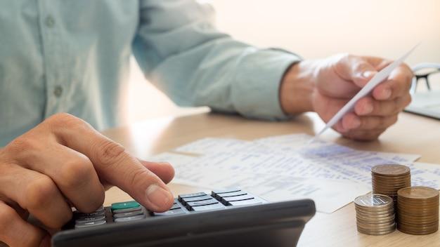 El hombre de negocios está estresado por los problemas financieros, use una calculadora para calcular el costo de los recibos colocados sobre la mesa