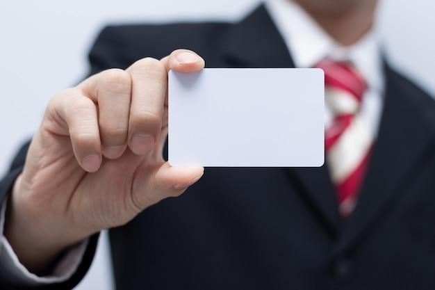 Hombre de negocios con la etiqueta de la identificación de la maqueta de la tarjeta de presentación en la tierra de la parte posterior del blanco.