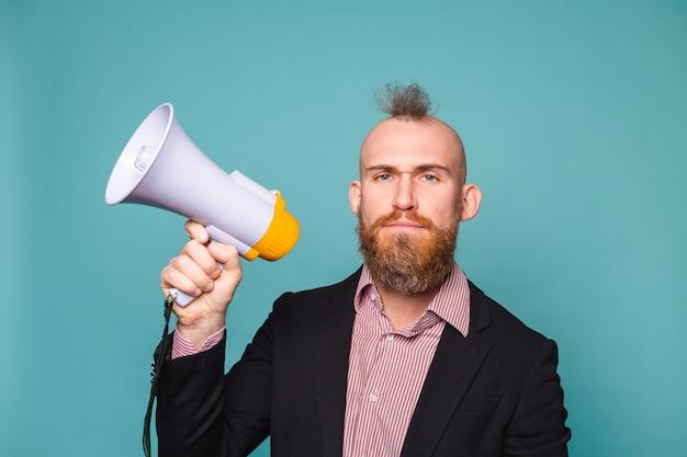 Hombre de negocios europeo barbudo en traje oscuro aislado, con megáfono