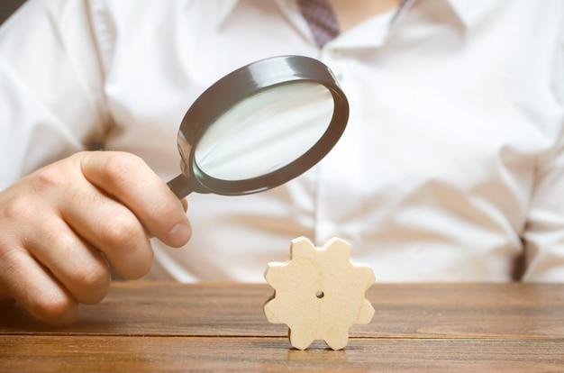 El hombre de negocios examina un engranaje de madera a través de un vidrio