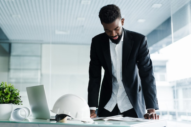 Hombre de negocios exitoso. apuesto joven africano e parado en la oficina creativa