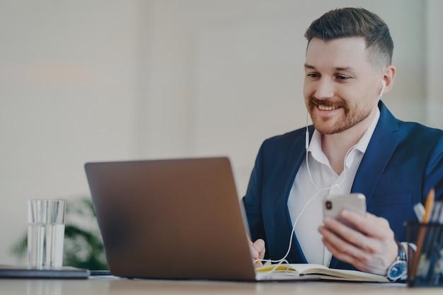 Hombre de negocios exitoso en auriculares haciendo videollamadas en una computadora portátil, sosteniendo un teléfono inteligente y hablando a través de una videoconferencia en la oficina o en el hogar, el jefe tiene una reunión de negocios remota con un socio o cliente