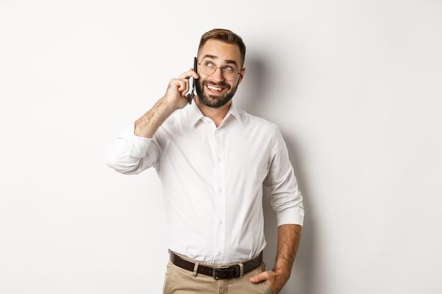Hombre de negocios exitoso en gafas hablando por teléfono móvil, mirando satisfecho y sonriendo, de pie