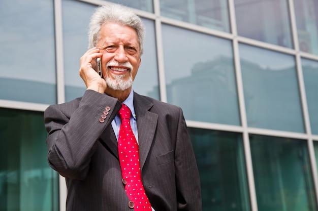 Hombre de negocios exitoso está hablando en su teléfono inteligente