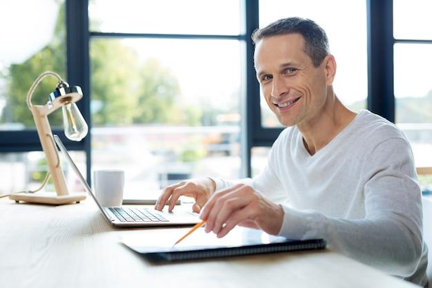 Hombre de negocios exitoso. hombre agradable positivo encantado mirándote y sonriendo mientras está sentado en su oficina