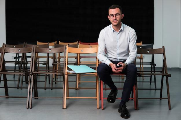 Hombre de negocios exitoso joven sentado en la silla
