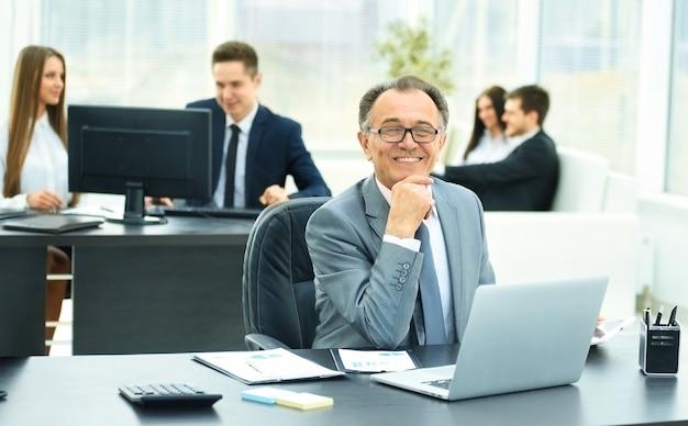 Hombre de negocios exitoso en el lugar de trabajo con el portátil en una oficina moderna en el fondo del equipo empresarial