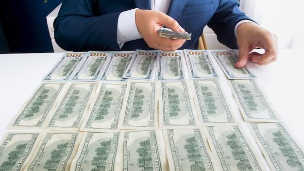 Hombre de negocios exitoso poniendo dinero en el escritorio de la oficina mientras los cuenta