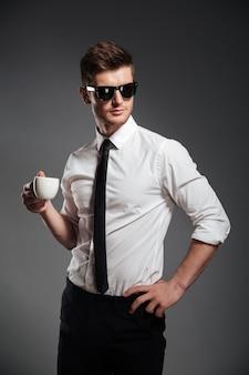 Hombre de negocios exitoso en ropa formal con taza de café mientras está de pie