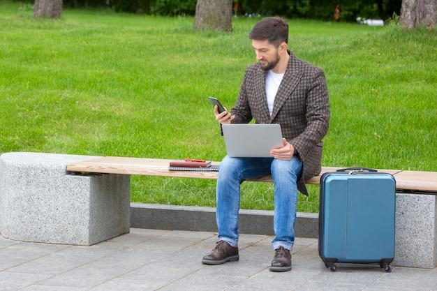 Hombre de negocios exitoso se sienta en un banco de la ciudad y se dedica a negocios con documentos y computadora portátil