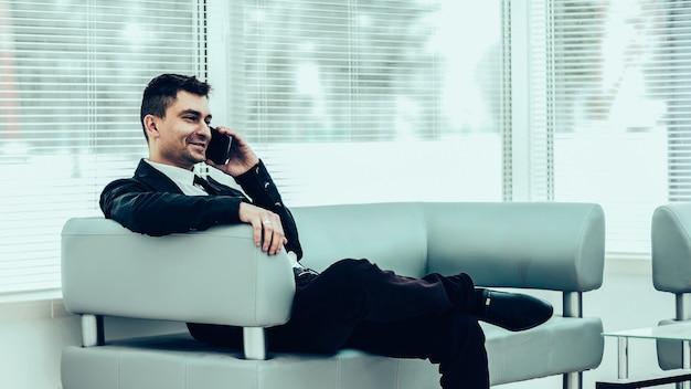 Hombre de negocios exitoso se sienta en el vestíbulo de una oficina moderna y