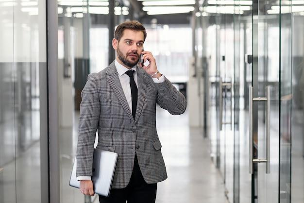 Hombre de negocios exitoso tener conversación telefónica mientras está de pie en el pasillo de la oficina vacía. hombre banquero profesional en traje hablando por teléfono móvil durante las vacaciones de trabajo.