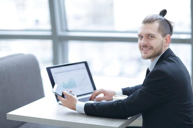 Hombre de negocios exitoso está tomando café, sentado en su escritorio .pausa para el café