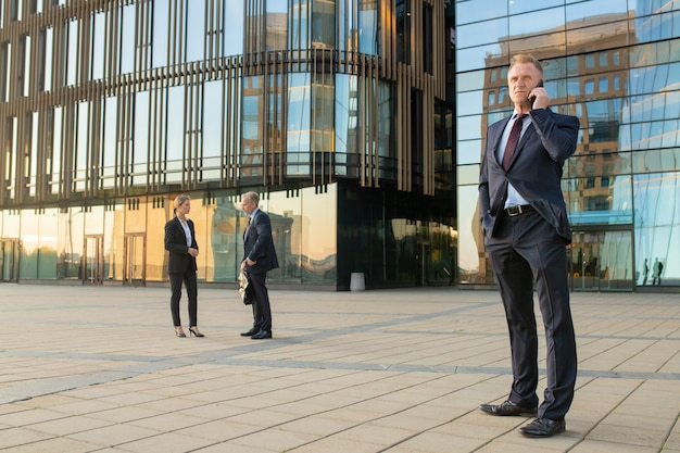 Hombre de negocios exitoso con traje de oficina, hablando por teléfono móvil al aire libre. los empresarios y la fachada de cristal del edificio de la ciudad en segundo plano. copie el espacio. concepto de comunicación empresarial