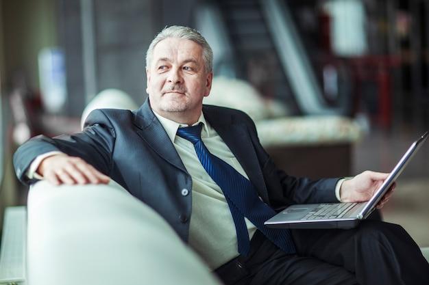 Hombre de negocios experimentado que trabaja en la computadora portátil que se sienta en el sofá en una oficina privada