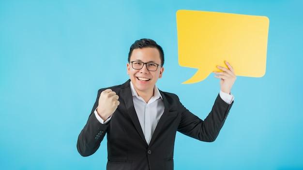 Hombre de negocios feliz asiático que sonríe y que sostiene el bocadillo de diálogo amarillo aislado en fondo azul