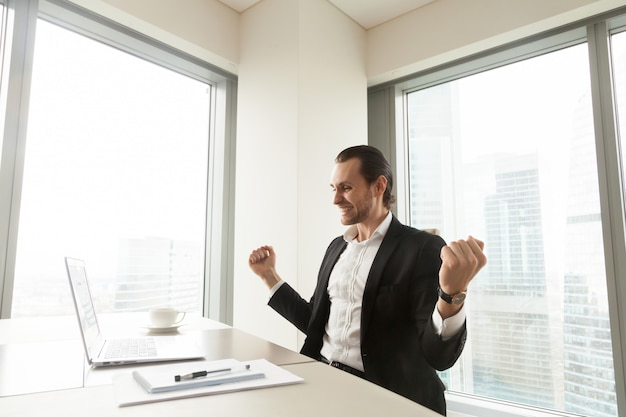 Hombre de negocios feliz delante de la computadora portátil