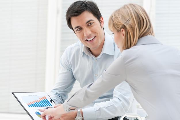 Hombre de negocios feliz discutir con su colega en la tabla de crecimiento exitosa
