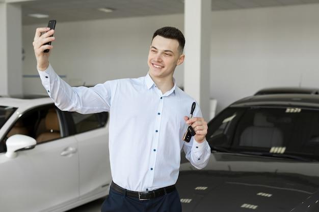 Hombre de negocios feliz haciendo selfie foto sosteniendo las llaves delante de su auto nuevo en la sala de exposición