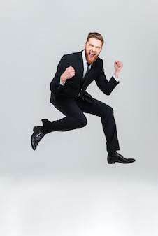 Hombre de negocios feliz de longitud completa en traje negro saltando en estudio y mirando a cámara con la boca abierta. fondo gris aislado