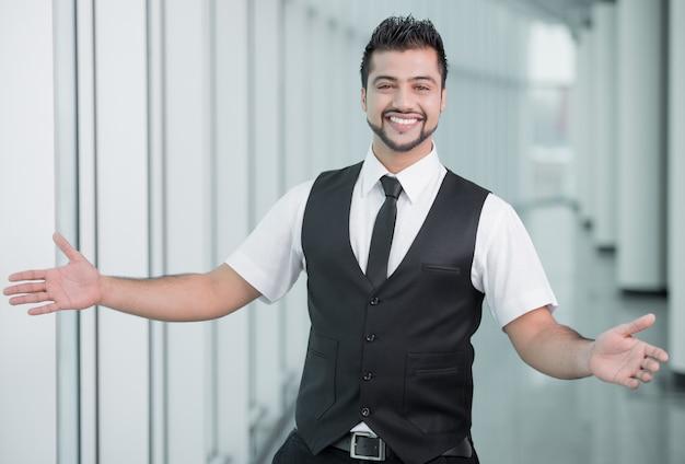 Hombre de negocios feliz con las manos separadas para dar la bienvenida.