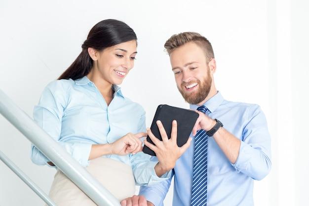 Hombre de negocios feliz y mujer usando tableta
