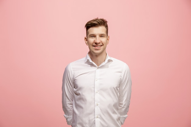 Hombre de negocios feliz de pie y sonriendo contra rosa