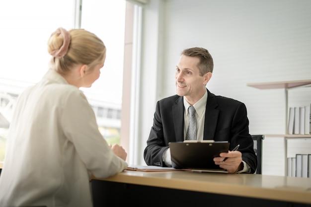 Hombre de negocios feliz que firma la firma en el documento en el escritorio y hablando con la empleada en la sala de oficina
