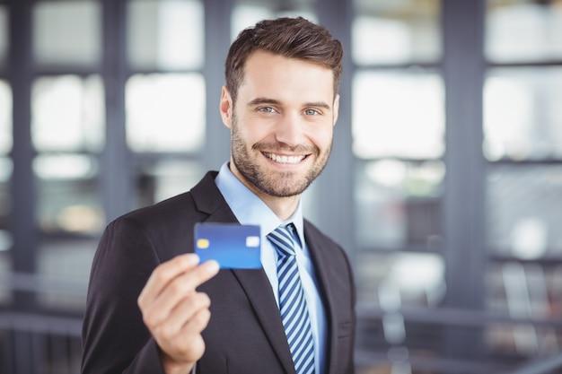 Hombre de negocios feliz que muestra la tarjeta de crédito