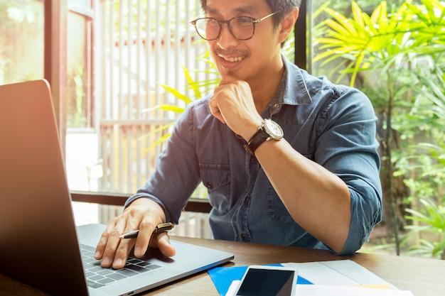 Hombre de negocios feliz que sonríe mientras que trabaja en la computadora portátil