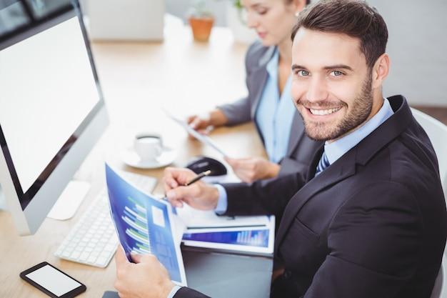Hombre de negocios feliz que sostiene el escritorio de la computadora de gráfico