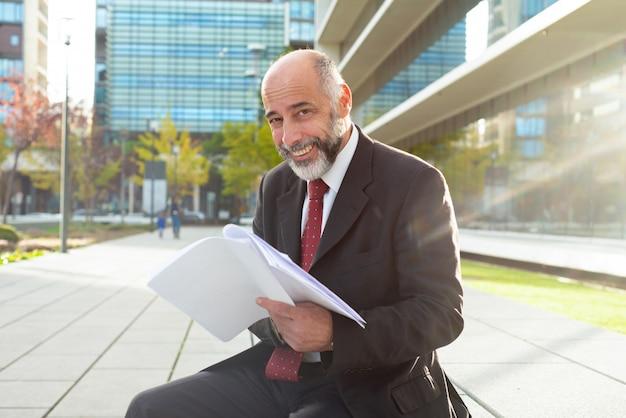 Hombre de negocios feliz que sostiene los papeles al aire libre