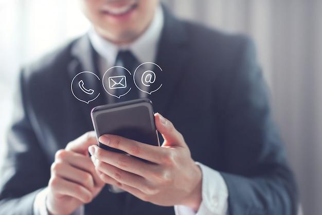 Hombre de negocios feliz que sostiene el teléfono inteligente móvil con el icono (correo, teléfono, correo electrónico).