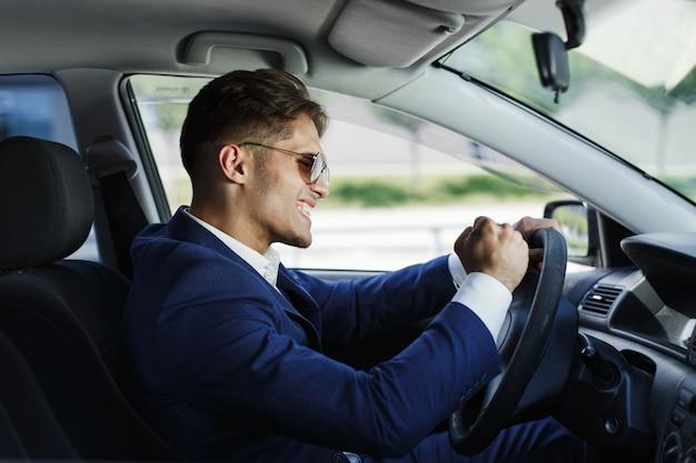 El hombre de negocios feliz se sienta muestra sus emociones que se sientan en el volante dentro del coche