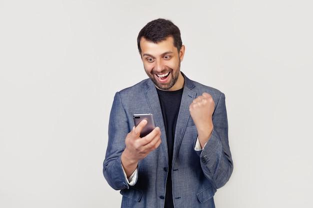 Hombre de negocios feliz sosteniendo un teléfono inteligente y celebrando su éxito