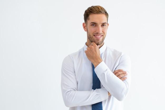 Hombre de negocios feliz tocando barbilla y mirando a cámara